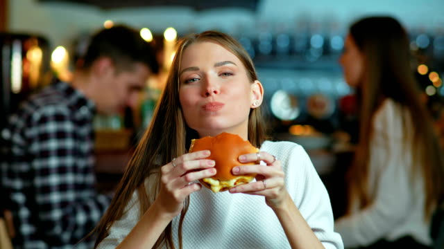 vídeos de stock e filmes b-roll de young happy woman eating tasty fast food burger in cafe - eating