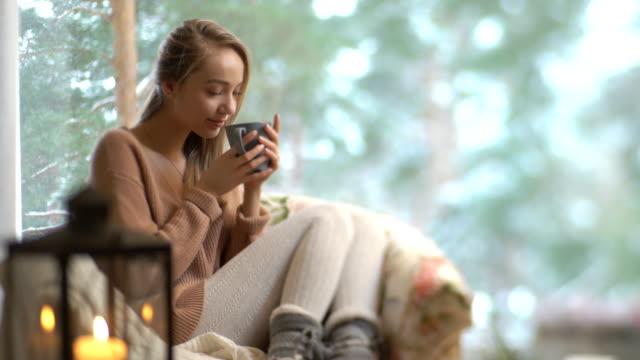 vidéos et rushes de profitez de la jeune femme heureuse de coupe de la séance de café chaud maison par la grande fenêtre avec fond d'arbre neige hiver - thé boisson chaude