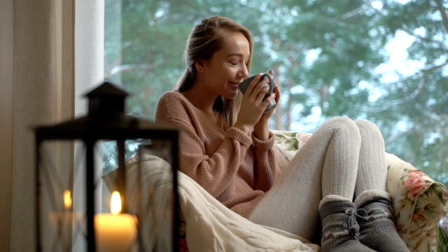 Young happy woman enjoy of cup of hot coffee sitting home by the big window with winter snow tree background Cozy winter lifestyle. Happy young woman enjoy of cup of hot coffee sitting home by the big window with winter snow tree background. heat temperature stock videos & royalty-free footage