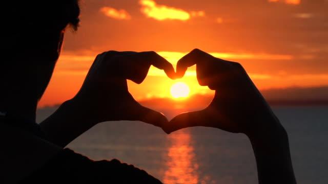 Junge Frau glücklich bildet ein Herz mit ihren Fingern und genießt schöne und epische Sonnenuntergang mit goldenen Sonnenlicht – Video