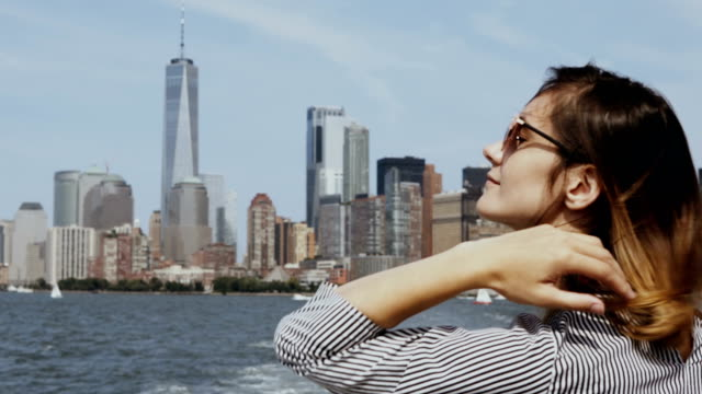 Young happy woman go for a boat through the East river in New York, America, looking on Manhattan and enjoying video