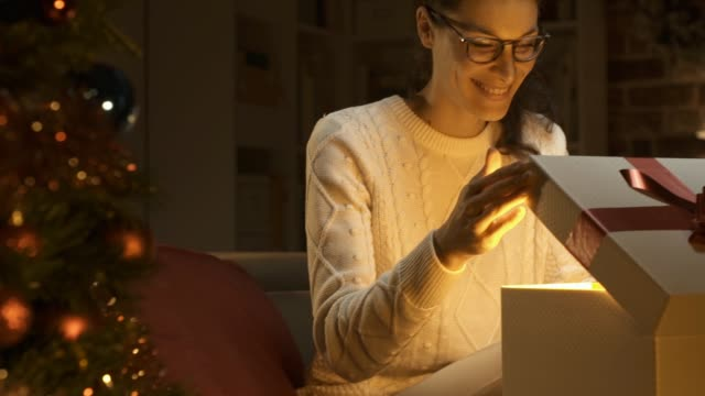Young happy woman opening a beautiful Christmas gift