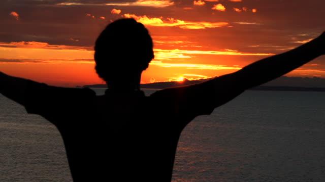 Froh, dass Frau wirft ihr junge Arme erfolgreich am Strand und genießt schöne und epische Sonnenuntergang mit goldenen Sonnenlicht – Video