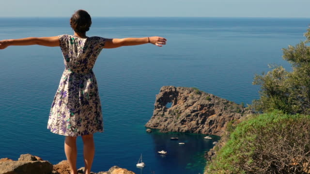 young happy woman reaches top of the mountain cliff and raises her arms successfully against the beautiful ocean landscape - summer background стоковые видео и кадры b-roll