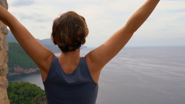 Junge Frau glücklich erreicht oben auf der Klippe und hebt ihre Arme erfolgreich gegen die schönen Meer-Landschaft – Video