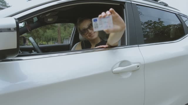 vídeos y material grabado en eventos de stock de mujer joven feliz mostrando su nueva licencia de conducir - carne