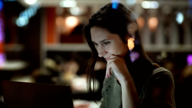 Young happy woman sitting on the cafe and using the laptop. View inside the window on female surfing the Internet video