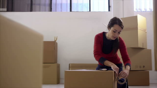 stockvideo's en b-roll-footage met young happy woman smiling at home during move with boxes - stempel