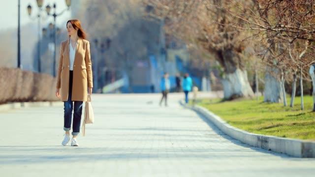 vídeos y material grabado en eventos de stock de joven mujer feliz camina en la plaza a principios de la primavera. la chica está vestida con estilo, disfruta de la vida. - abrigo