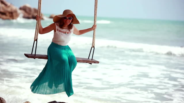 Young happy woman wearing hat and sunglasses relaxing at swing at tropical ocean beach. Beautiful girl sitting on swing and enjoying summer vacation or holiday. 1920x1080 video