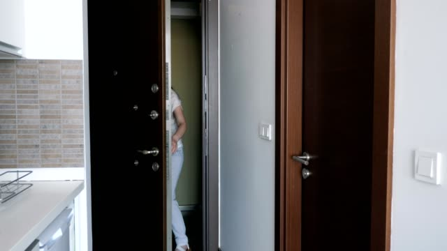 Young happy woman with a suitcase enters the rented apartment at vacation.