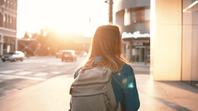 vídeos de stock e filmes b-roll de young happy woman with backpack walking in downtown alone. beautiful female turns and smiling at camera - mochila saco