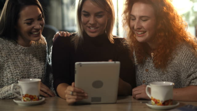 Young happy women using touchpad in a cafe and laughing. video
