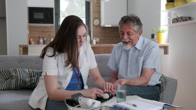 Jonge gezondheidswerker meten bloedglucose van een senior man at Home video