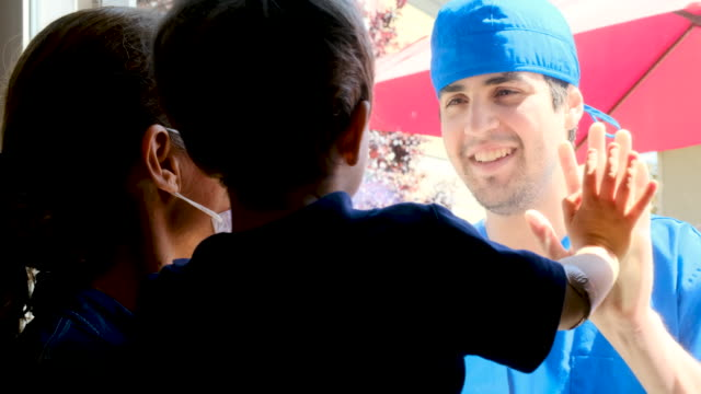 若い医療従事者は、伝染の可能性を避けるためにそれらを分離する窓ガラスで彼の息子を見てポーズ - covid 19点の映像素材/bロール