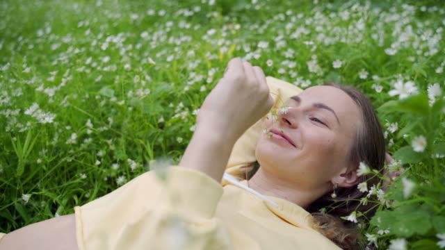 vídeos y material grabado en eventos de stock de una chica joven, sana y hermosa está acostada en la hierba y olfateando flores - acostado