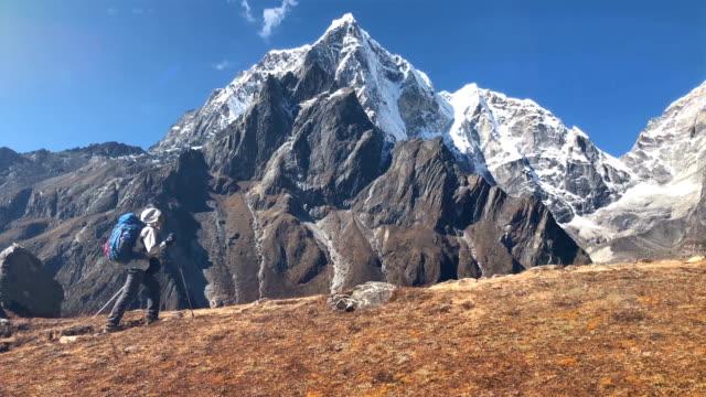 高地エベレストベースキャンプ(ebc)ルートの間にトレッキングポールハイキングを使用して若いハイカーバックパッカー女性は、背景に雪トブッシュ6495m山頂を持っています。極端にアクティ - 耐久力点の映像素材/bロール