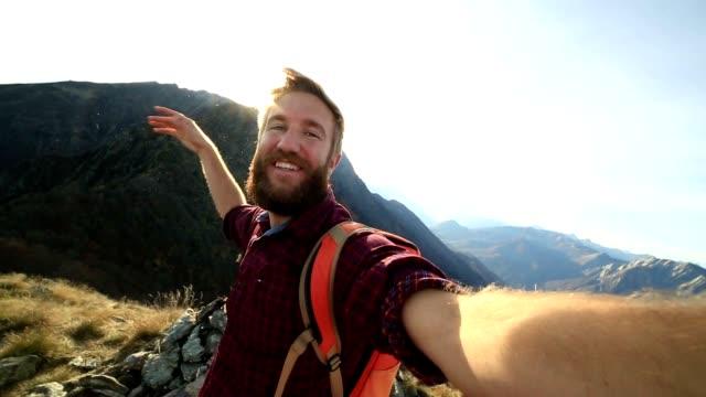 vidéos et rushes de jeune randonneur prend selfie du sommet de la montagne - culture des jeunes
