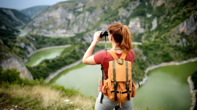 Young hiker woman reaches the top of hill, enjoys view