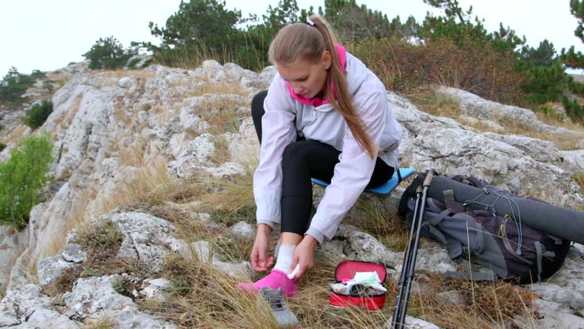 Young hiking woman sprained ankle using first aid kit applying bandage video