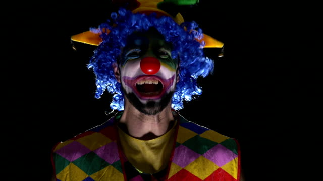 Young hilarious clown making scary faces and laughing video