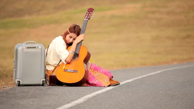 Young hippie woman with guitar and backpack sitting on a countryside road video