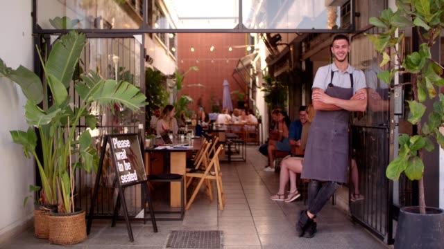 unga hipster café manager står på butiken entré - liten bildbanksvideor och videomaterial från bakom kulisserna