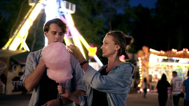 Young hipster couple are having time together in the amusement park at night. Feeding each other with pink cotton candy. Front view Young hipster couple are having time together in the amusement park at night. Feeding each other with pink cotton candy. Front view. date night romance stock videos & royalty-free footage