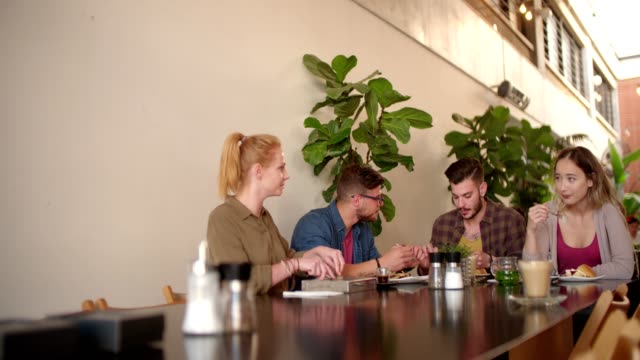Young hipster couples eating lunch at modern urban restaurant video