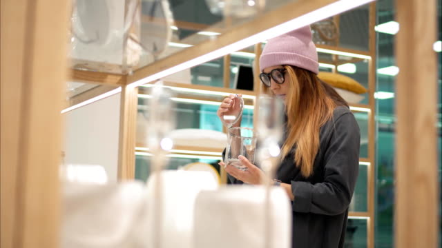 a young hipster female in fashion glasses chooses home accessories in the store - preppy fashion stock videos and b-roll footage