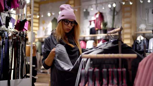 a young hipster female in fashionable glasses chooses new jacket. shopping mall - preppy fashion stock videos and b-roll footage