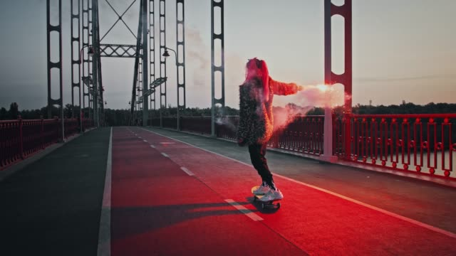 young hipster female in informal outfit is skateboarding on bridge holding burning red signal flare and waving it - funky video stock e b–roll