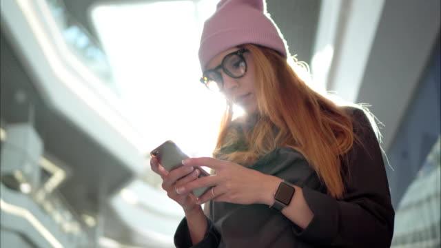 ein junge hipster-weibchen mit app auf dem smartphone in die großen einkaufszentrum - hipster stock-videos und b-roll-filmmaterial