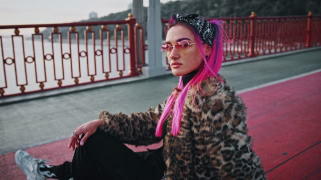 Young hipster female with pink hair, wearing informal outfit is sitting sideways on asphalt while posing on bridge