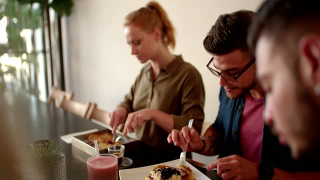 Young hipster friends eating brunch at modern cafe video