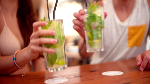 Young hipster friends toasting with mojito cocktails at summer bar Young hipster couple on tropical island summer vacations toasting with cocktails at beach bar celebratory toast stock videos & royalty-free footage
