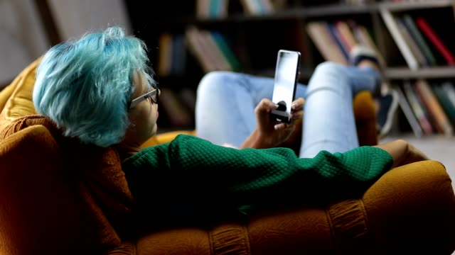 Young hipster girl using modern smartphone device Young hipster girl with blue hair and eyeglasses sitting in comfortable chair using modern smartphone device at home. Trendy young woman with mobile phone communicating with friends in social networks. Freelancer working from home via cellphone. blue hair stock videos & royalty-free footage
