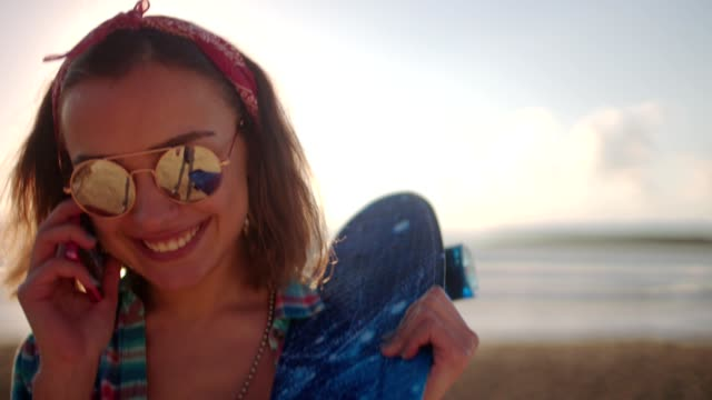 Young hipster girl with skateboard on beach talking on phone video