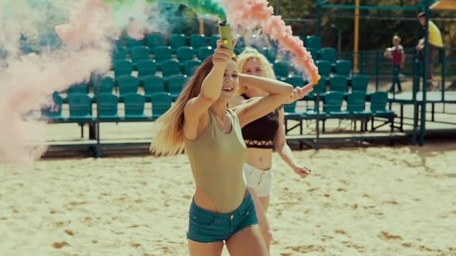 giovani ragazze hipster in pantaloncini corre in campo di sabbia agitando fumo colorato - bielorussia video stock e b–roll