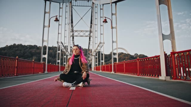 Young hipster lady with pink hair, in informal outfit is sitting in lotus pose on her skateboard, posing on bridge