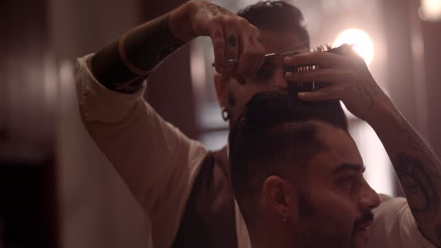 Young hipster man getting haircut by stylish old-fashioned barber video