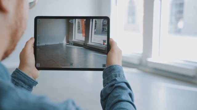 vídeos y material grabado en eventos de stock de joven hipster man en gafas de pie en oficina vacía y asignarlo con un software de realidad aumentada en una tableta. pantalla con la aplicación de la cámara tiene puntos de seguimiento para el software de vídeo. - propiedad inmobiliaria