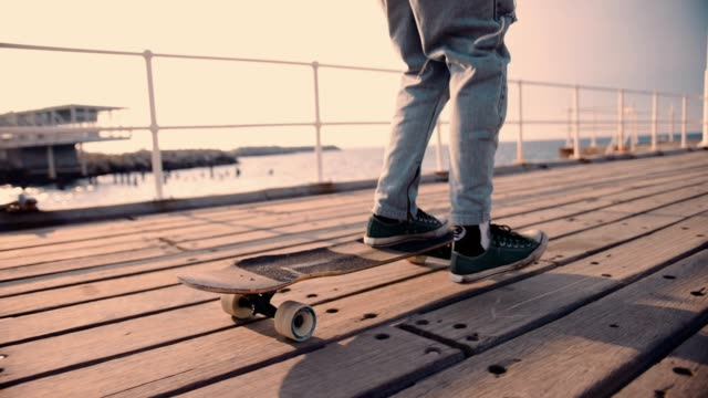 Young hipster man longboarding on urban jetty Young hipster fashionable teenage boy skateboarding with longboard over the sea on urban jetty skateboarding stock videos & royalty-free footage