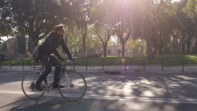 young hipster man riding bike in park on a road with trees in rome city centre wearing sunglasses on sunny day slow motion camera car steadycam - rower filmów i materiałów b-roll