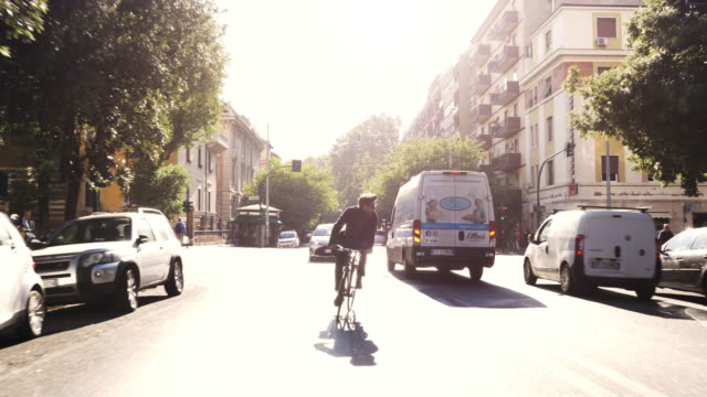 Young hipster man riding bike in traffic on a road with trees in Rome city centre wearing sunglasses on sunny day slow motion camera car steadycam