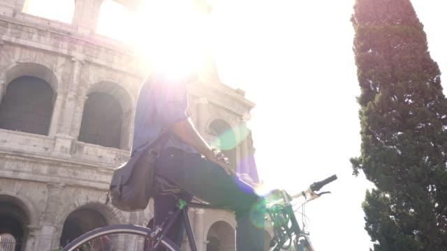 年輕的時髦男子騎自行車步行在羅馬城市中心在陽光明媚的日子慢動作 steadycam - 廣場 個影片檔及 b 捲影像