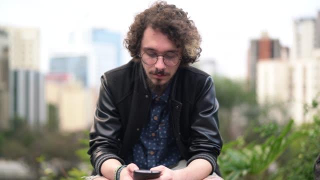 junge hipster mann mit mobilen portrait - hipster person stock-videos und b-roll-filmmaterial