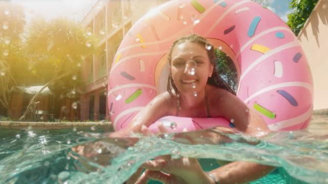 unga hipster tusenåriga flicka i stänkade donut flyta vid poolen, leende titta på kamera. ung lycklig kvinna koppla av på uppblåsbar pool leksak i blå pool på solig dag. - inflatable ring bildbanksvideor och videomaterial från bakom kulisserna