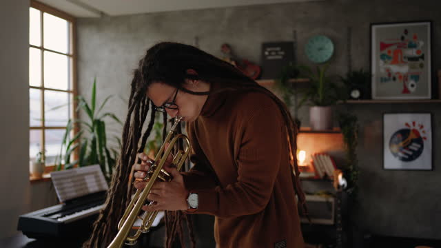 Young hipster musician with dreadlocks playing trumpet in his home office studio during pandemic video