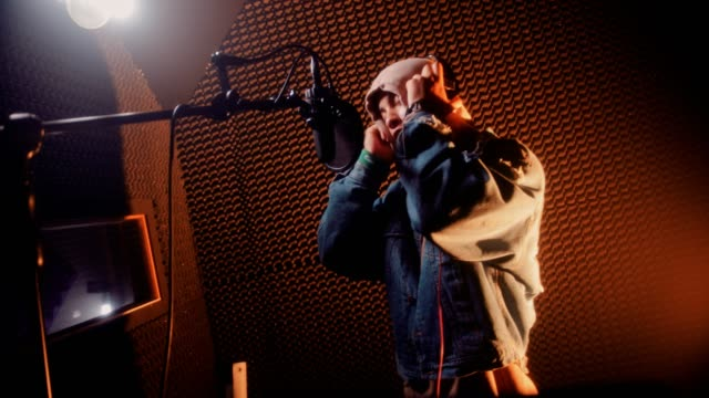 Young hipster singer performing and recording songs at music studio